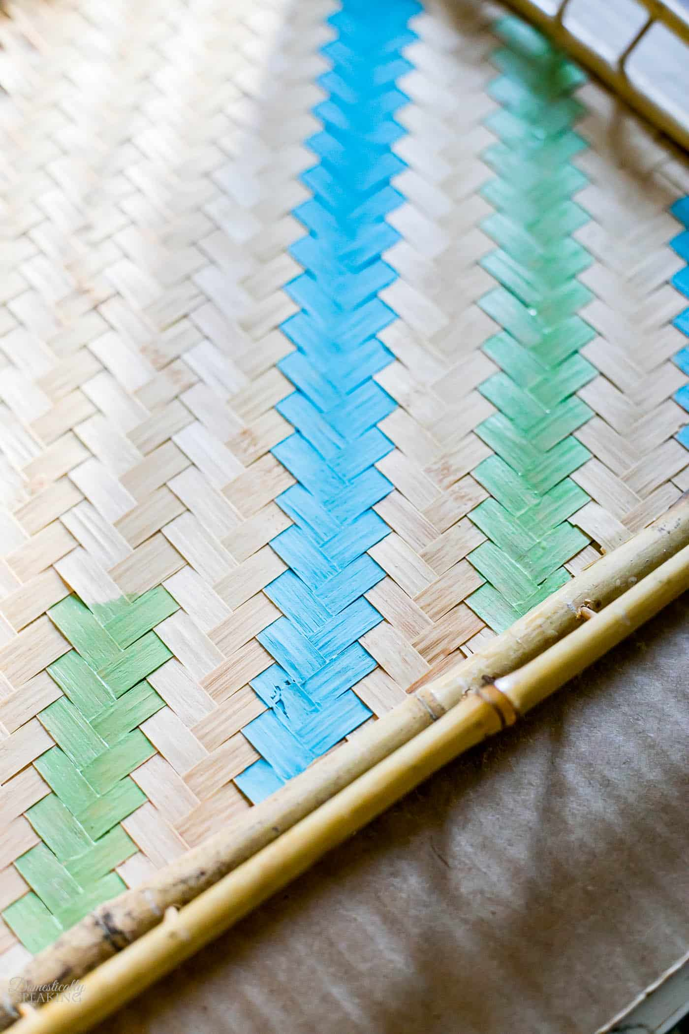 Painting stripes on a thrift store rattan tray in blue and green.