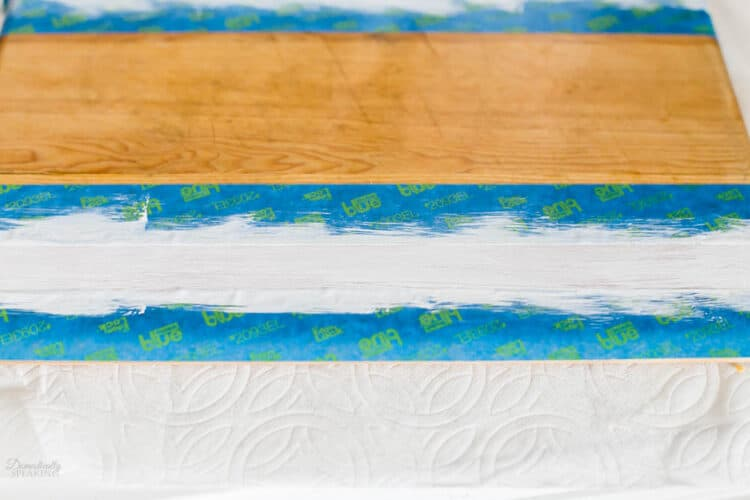 Painter's tape on wood board with white paint.
