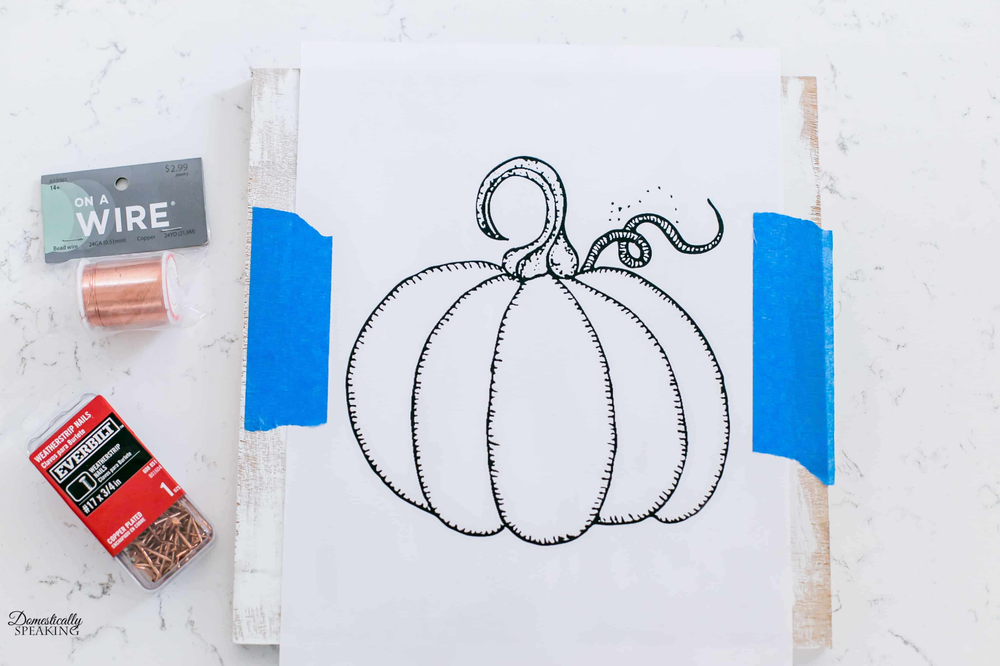 Attach the printed pumpkin image to the wood with painter's tape.