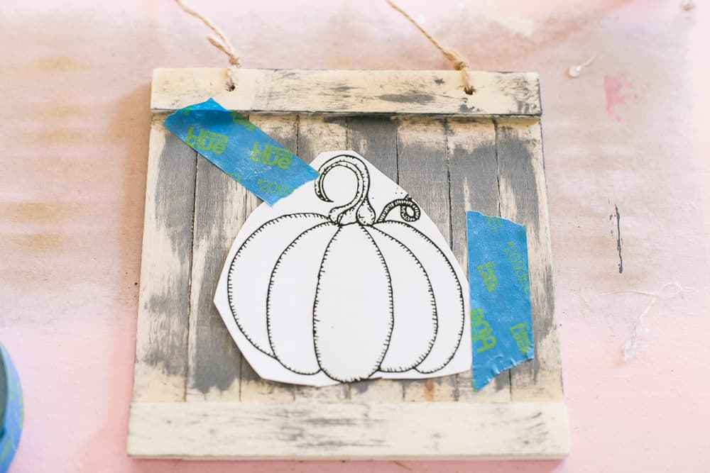 Taping a pumpkin image onto the painted sign.