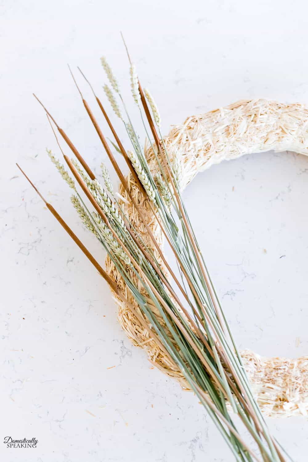 Adding cattails and wheat to the fall wreath.