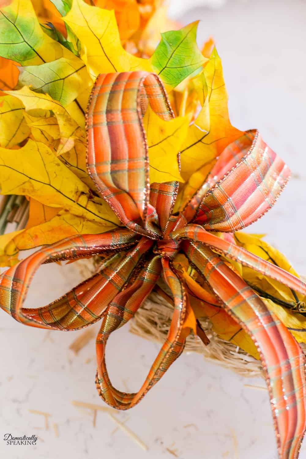 Adding the fall wire ribbon to the wreath.